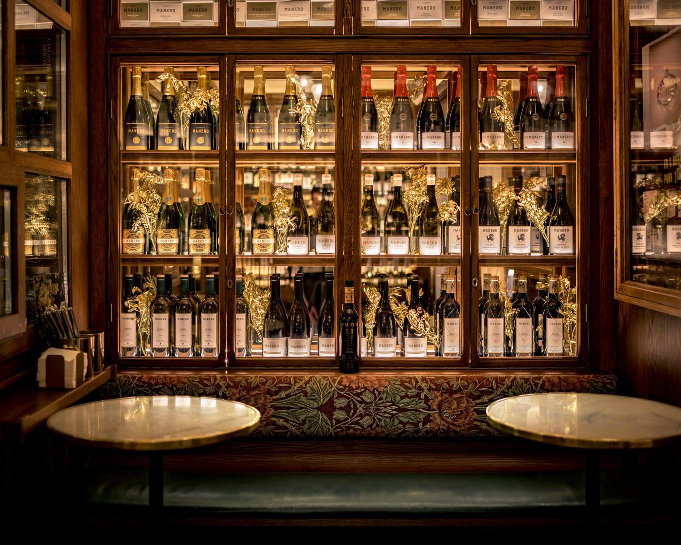 Vitrina con botellas en la entrada de Bar Manero Alicante