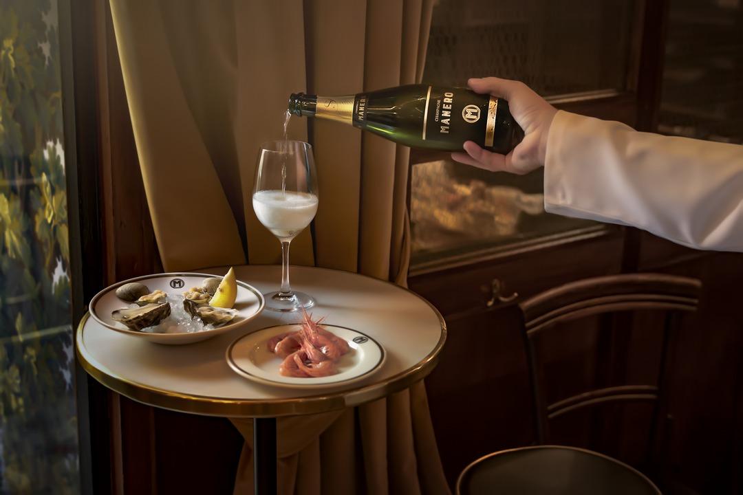 Platos de ostras y gamba roja acompañado de copa de champagne en El Singular Manero.